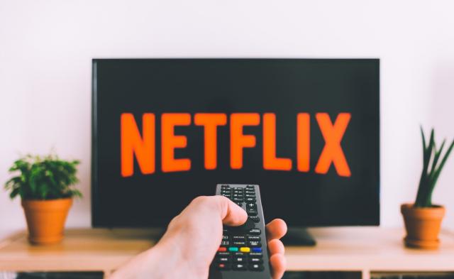 Télévision affichant le logo Netflix en fond avec une personne tenant une télécommande dans sa main. Cecic montre que Netflix est maintenant disponible sur tous les écrans
